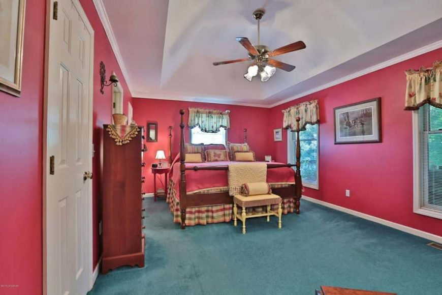 Country style master bedroom featuring red walls and green carpet flooring. It offers a large classy bed along with cabinetry on the side.