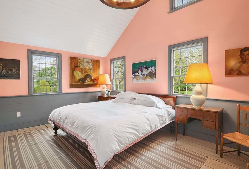Country style master bedroom featuring orange walls and hardwood flooring topped by an area rug, along with a tall white ceiling. The bed is lighted by table lamps on both sides.