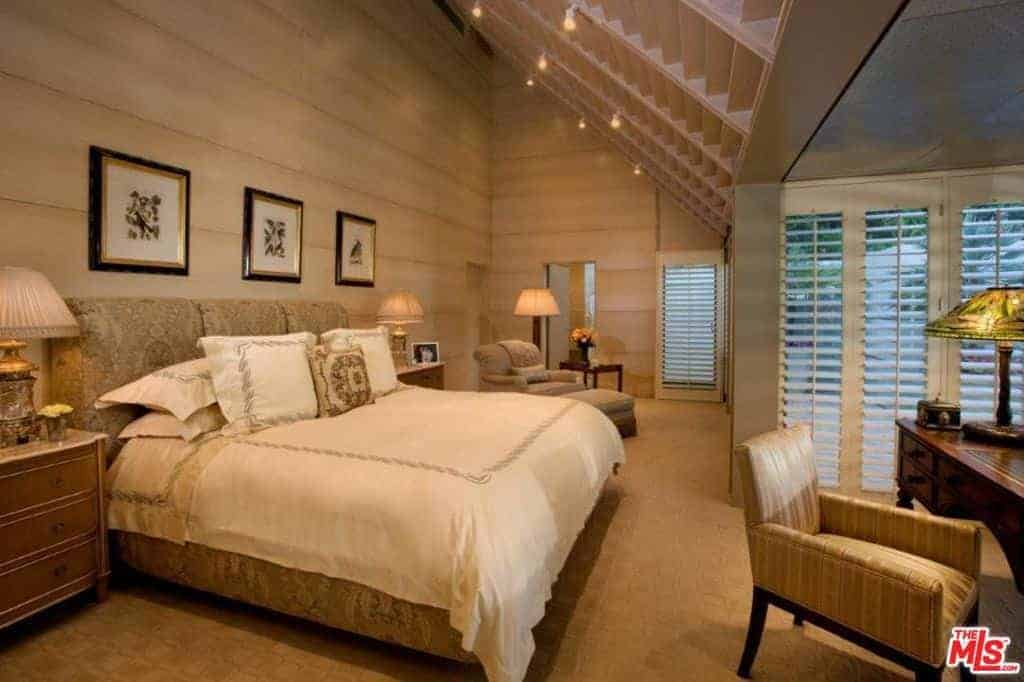 Master bedroom featuring a gorgeous large bed set on the room's carpet flooring. The room also offers an office desk with a table lamp.