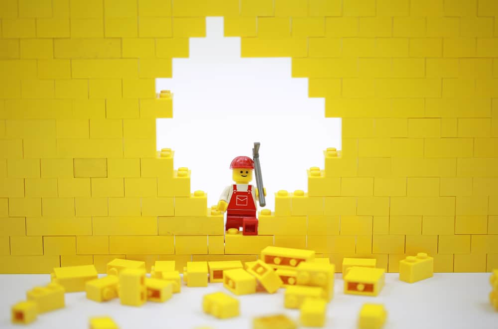 Yellow building bricks toy - a wall being broken down