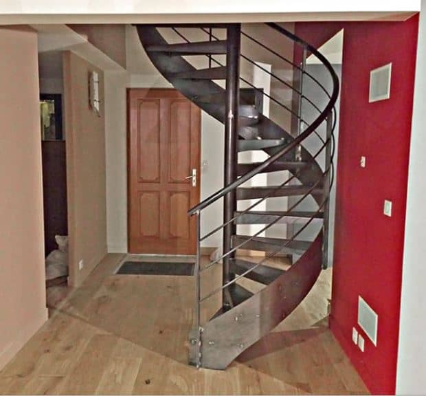The brown wooden door leads into this industrial-style foyer that is dominated by a large metal spiral staircase that solidifies its industrial-style claim. This is paired with hardwood flooring and a red wall that contrasts the fray metallic hue of the stairs.