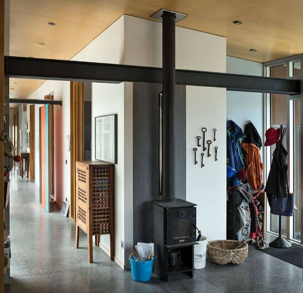 The warm and welcoming demeanor of this industrial-style foyer is due to the freestanding black iron fireplace near the mudroom that is filled with jackets, hats and bags. This pairs well with the gray industrial-style flooring that contrasts the light hue of the walls.