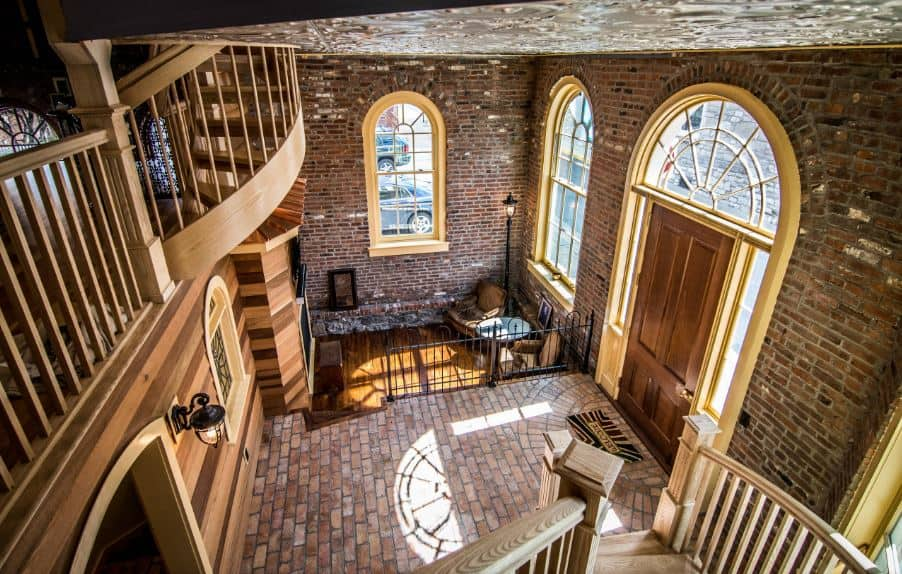 This charming industrial-style foyer has red bricks on its walls and floor that is illuminated by the side lights and arched transom window above the wooden main door that matches with the wooden stairs. Across from it is a wrought iron fence that separates the foyer from the living room.