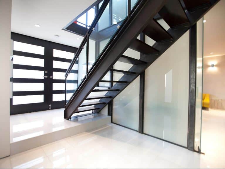The highlight of this industrial-style foyer is the metal staircase that looks like it belonged in a factory. It has a dark metallic hue to it that matches with the dark hue of the main door with frosted glass panels that match the frosted glass walls of the staircase.