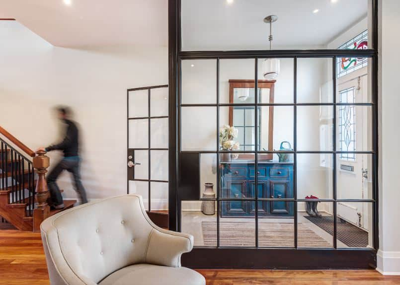 This charming industrial-style foyer is enclosed with glass walls and a glass door from the rest of the house. It has a white main door that has stained glass panels on it as well as in the transom window above that brings in natural lighting for the blue cabinet on the side.