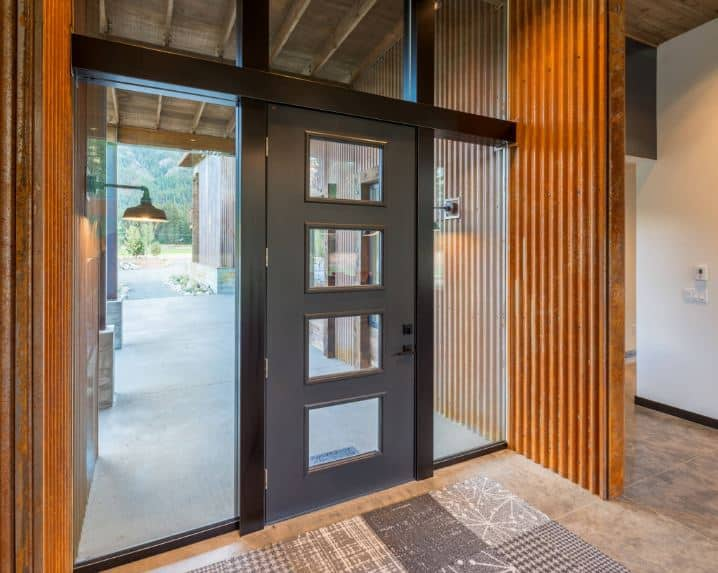This is an industrial-style foyer with rusty tin roofing material used on the walls adjacent to the gray main door that is framed with glass panels on three sides that bring in an abundance of natural lighting to the beige marble flooring topped with a gray patterned area rug.