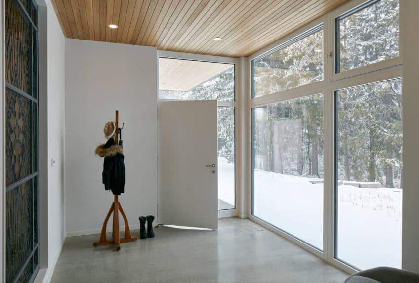 This industrial-style foyer has glass walls to showcase the beauty of the landscape scenery outside filled with snow and trees. The simple industrial-style flooring is adorned with a standing wooden rack for jackets and hats that pairs well with the wooden ceiling.