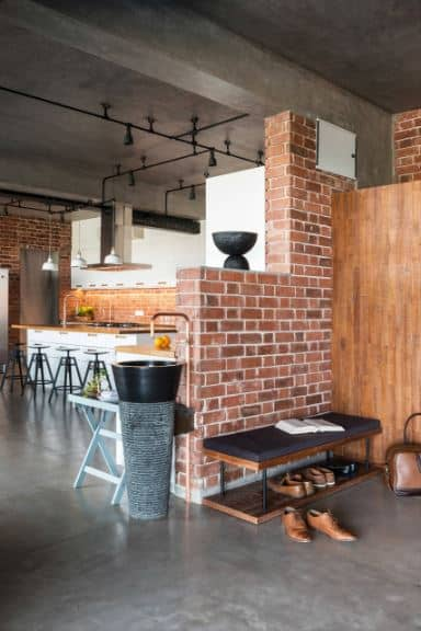 This simple and small industrial-style foyer has the same red brick walls and gray concrete flooring and ceiling as the rest of the house. On one side is a wooden bench with a black cushion and a shelf at the bottom of it to serve as a shoe rack.