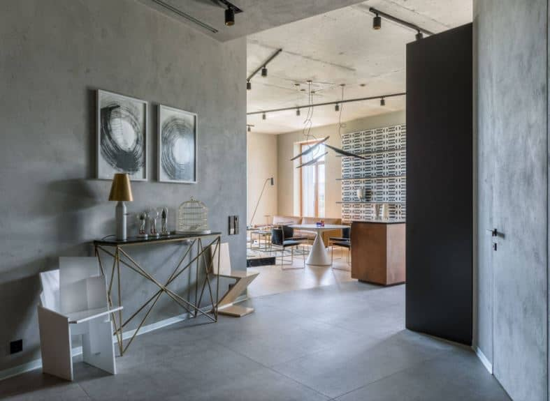 The gray main door that blends with the gray walls leads to this industrial style foyer that has concrete flooring and a modern console table bearing decors and a table lamp. The two paintings mounted on the concrete wall above the table adds to the aesthetic.