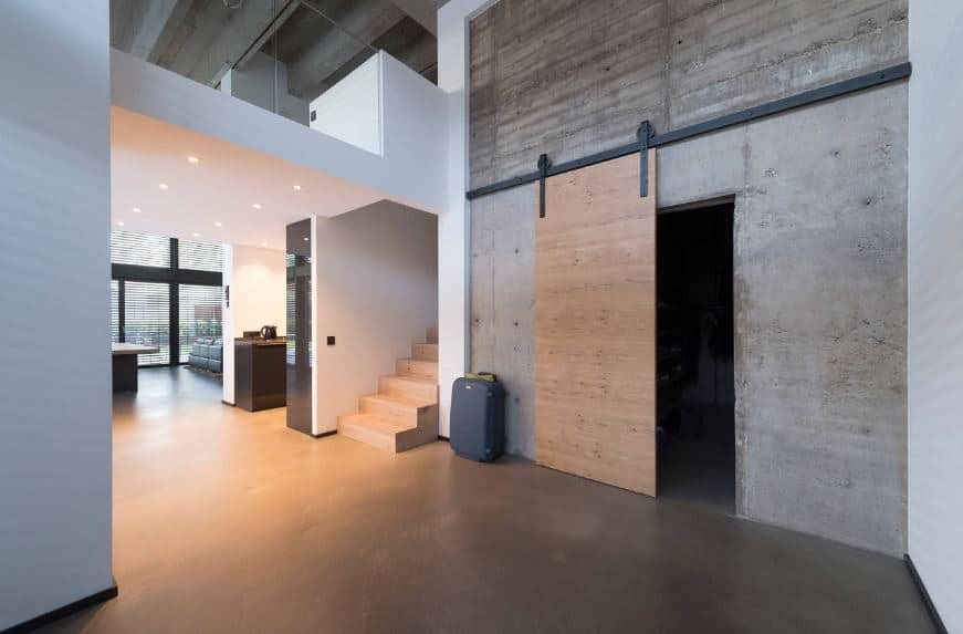 This wide industrial-style foyer has concrete flooring that pairs well with the concrete wall that supports the iron rung of the wooden sliding door that matches with the wooden stairs leading to the second level that has glass railings.