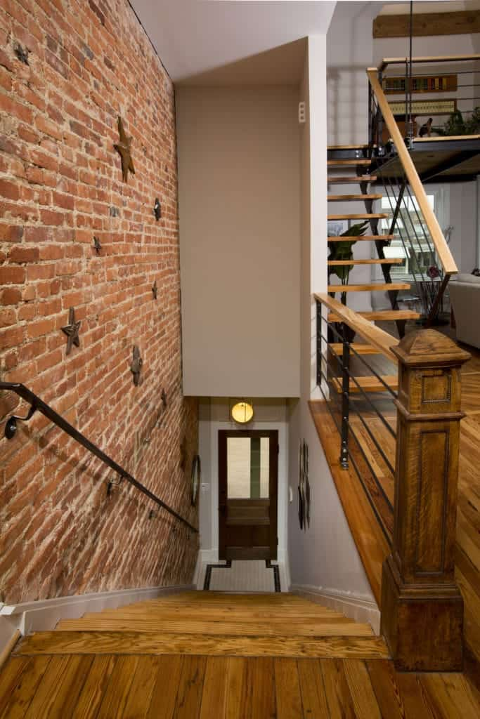 This industrial-style foyer has a wooden main door with a glass panel on it lit by an industrial-style wall lamp above. The small foyer directly leads to a wooden stairs that has a red brick wall on one side and white wall on the other side leading up to the rest of the house.
