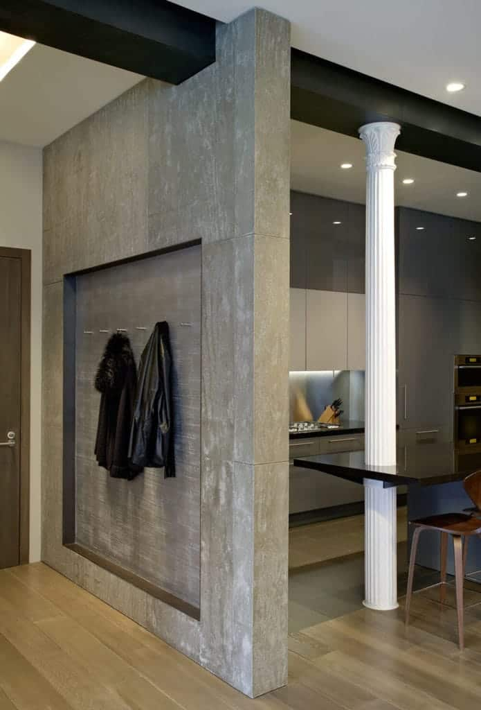This foyer is separated from the kitchen by a gray concrete wall that has an alcove with hooks that can be used as coat racks and hat racks for those who enter the brown wooden main door that contrasts the beige walls but complements the hardwood flooring.