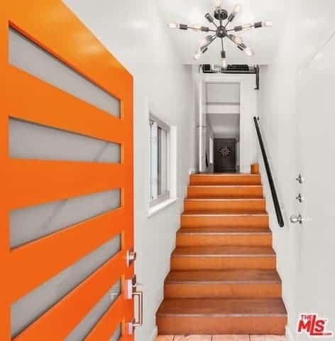 Upon entry of this bright orange front door that has frosted glass panels, you are welcomed with an industrial-style foyer that is narrow and has white walls and ceiling with an industrial-style chandelier above the terracotta stairs leading up to the rest of the house.