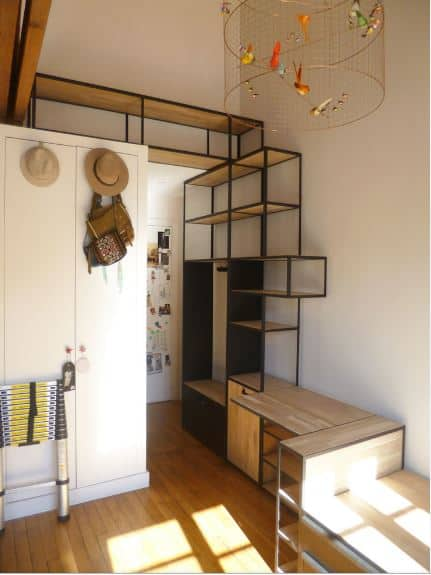 This small foyer is maximized with a large structure made of black iron and wooden shelves. This serves as a mudroom, sitting area, shoe rack, storage area and as a nice accent to the tall white walls that are contrasted by the hardwood flooring.