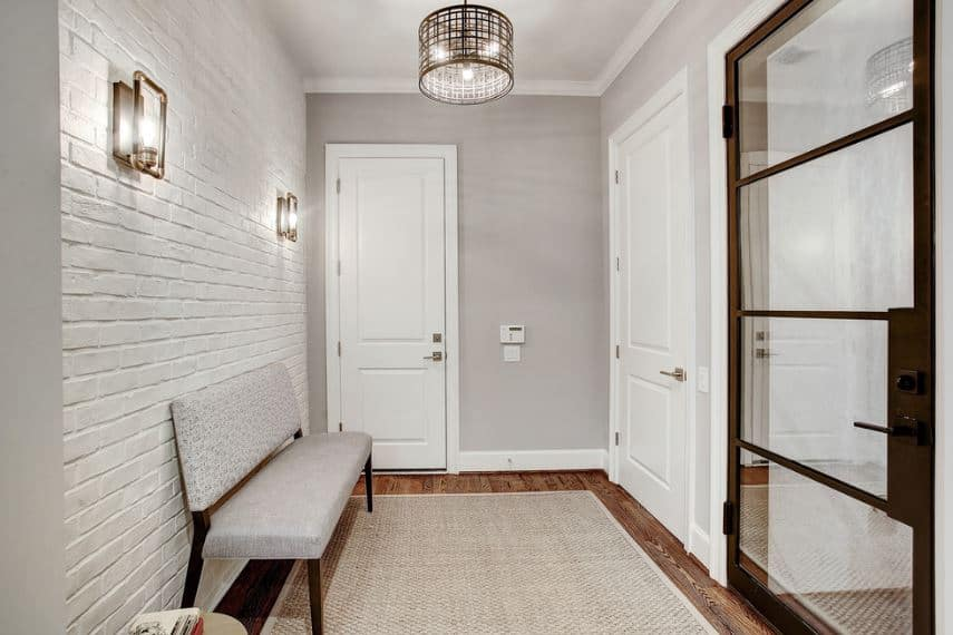 This simple industrial-style foyer has a textured white wall with a brick wall pattern adorned with a couple of wall-mounted lamps that match with the round pendant light from the light gray ceiling matching the walls and woven area rug as well as the cushioned bench.