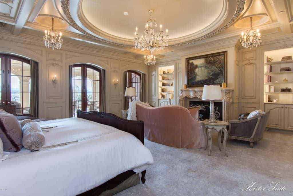 The luxury bedroom features a dark wood bed and a seating area by the fireplace designed with intricate details. It is illuminated by fancy chandeliers that hung from the round tray ceiling.