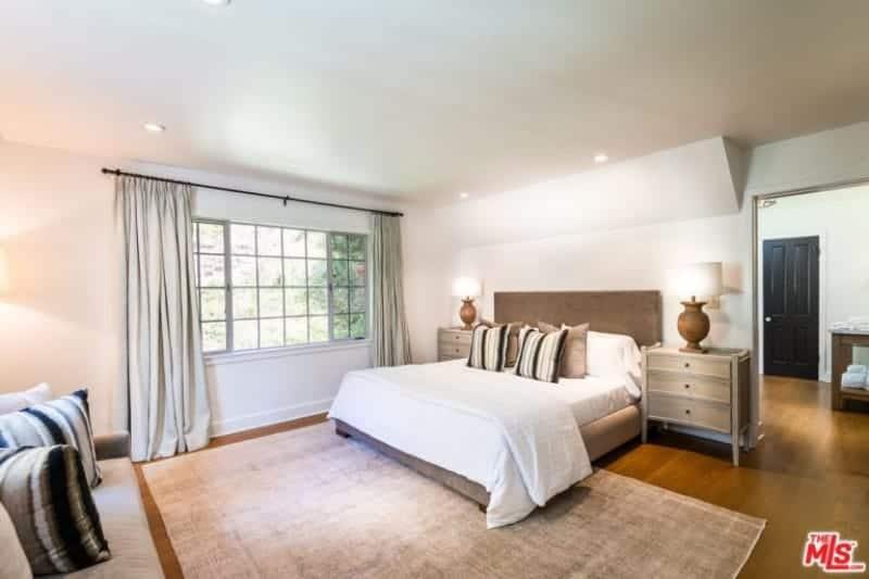 Grande chambre des maîtres avec plancher de bois franc surmonté d'un tapis.  La chambre a un lit confortable et un canapé confortable.