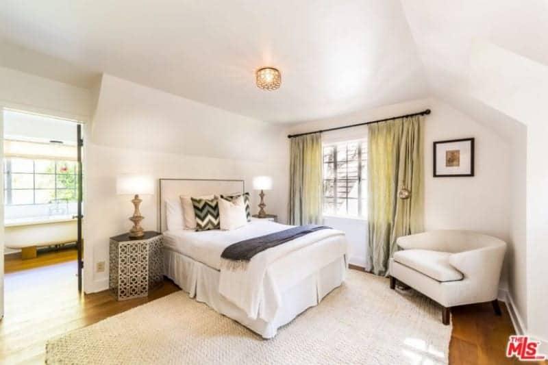 Grande chambre des maîtres avec parquet en bois franc et murs blancs.  La chambre dispose d'un lit double confortable ainsi que de sa propre salle de bain avec baignoire sur pieds.