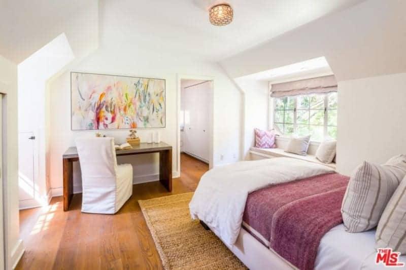 Chambre à coucher principale avec planchers de bois franc et murs blancs.  La chambre a un beau lit blanc avec une petite table à manger sur le côté.