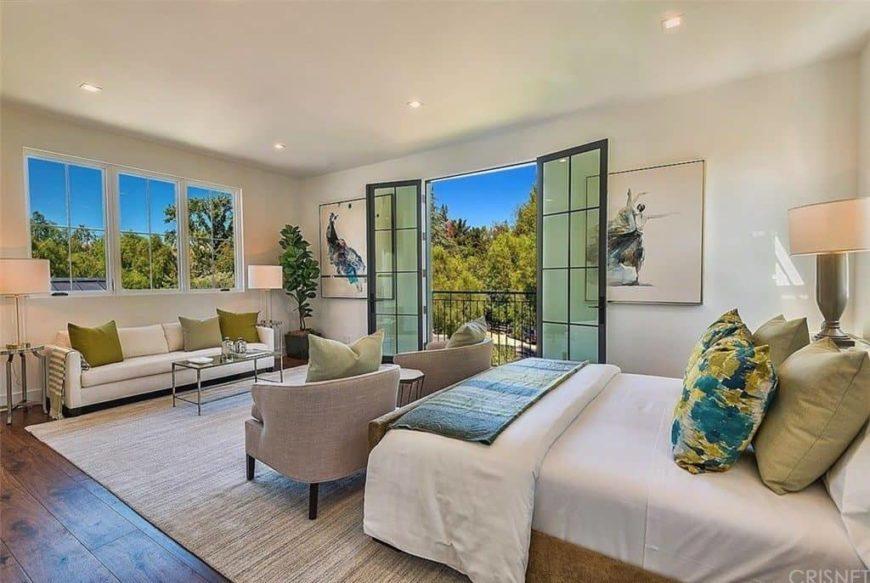Grande chambre des maîtres avec plancher de bois franc et plafond régulier.  Il propose un lit agréable avec un canapé blanc près des fenêtres éclairé par deux lampes de table.