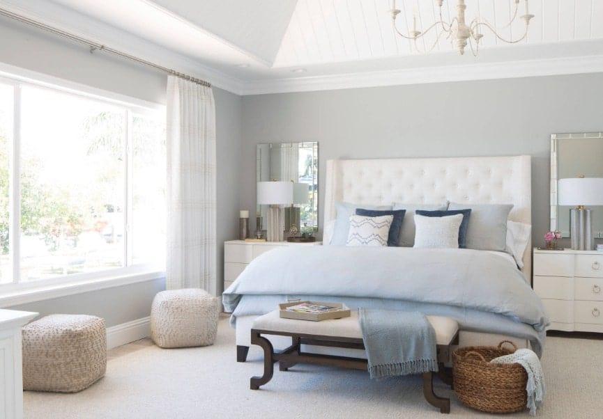 Chambre des maîtres lumineuse avec des murs gris et un plafond blanc.  La chambre a un grand lit et deux lampes de table, avec un magnifique lustre.