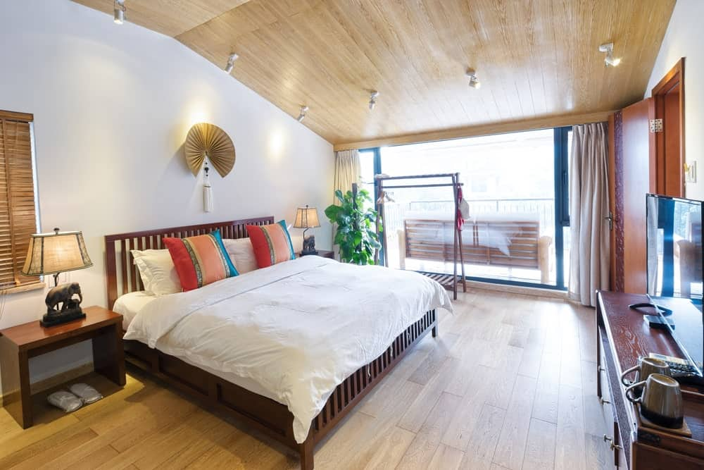 Cozy master bedroom with a wooden bed and nightstands topped with elephant table lamps. It is illuminated by white track lights that are mounted on the vaulted ceiling clad in light wood planks.