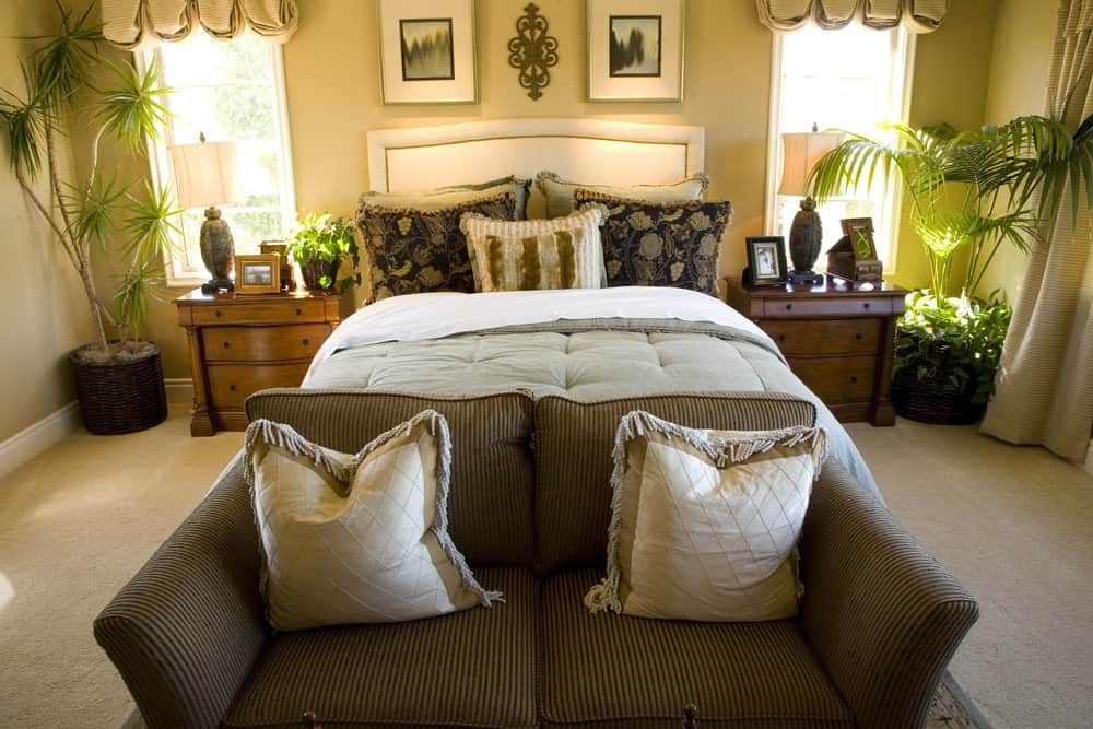 This master bedroom boasts a white leather bed and a striped couch topped with tasseled pillows. It has wooden nightstands and framed windows dressed in lovely beige valances.