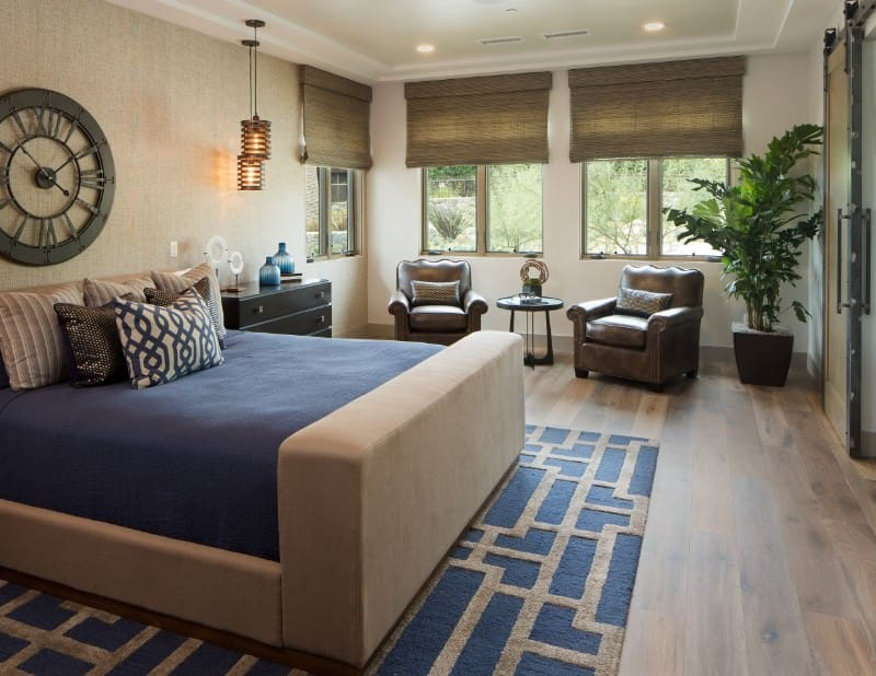 Stylish pendant lights hang over the black nightstand in this master bedroom with a seating area and a beige upholstered bed on an eye-catching blue rug topped with a round wall clock.