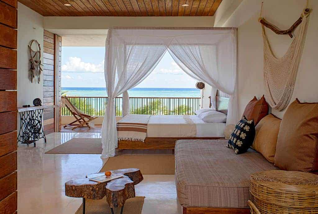 Tropical bedroom with a breathtaking beach view showcasing a canopy bed and a seating area on the side designed with a lovely boho tapestry. It has tiled flooring and wood plank ceiling fitted with recessed lights.