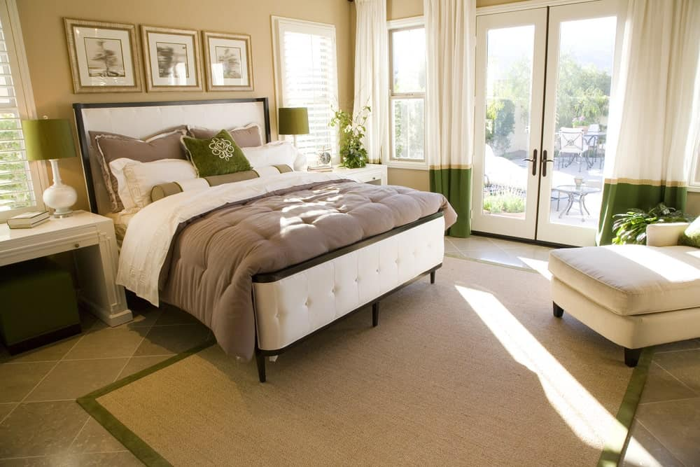 Beige master bedroom with subtle green accents from the curtains, throw pillow and lampshades that sit on white nightstands. It has a white chaise lounge and a tufted bed over a bordered jute rug and limestone flooring.