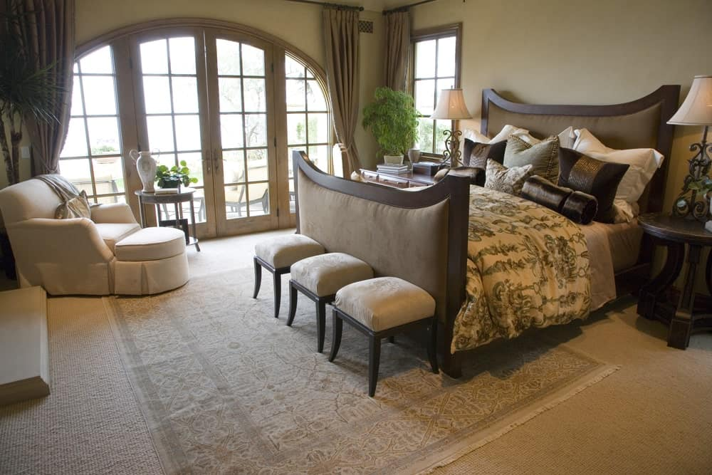 Tropical master bedroom features a white skirted lounge chair and upholstered bed with cushioned stools on its end that sit on a vintage area rug.