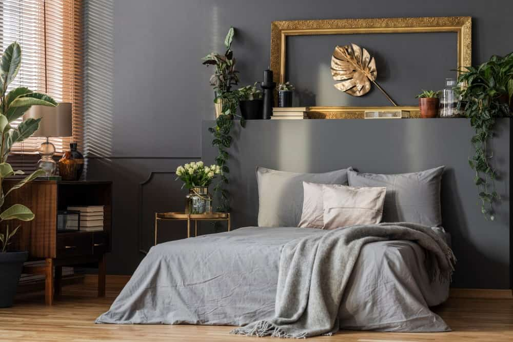 This master bedroom is decorated with potted plants and a lovely leaf wall art framed in ornate gold. It is mounted above the platform bed that's dressed in gray bedding.