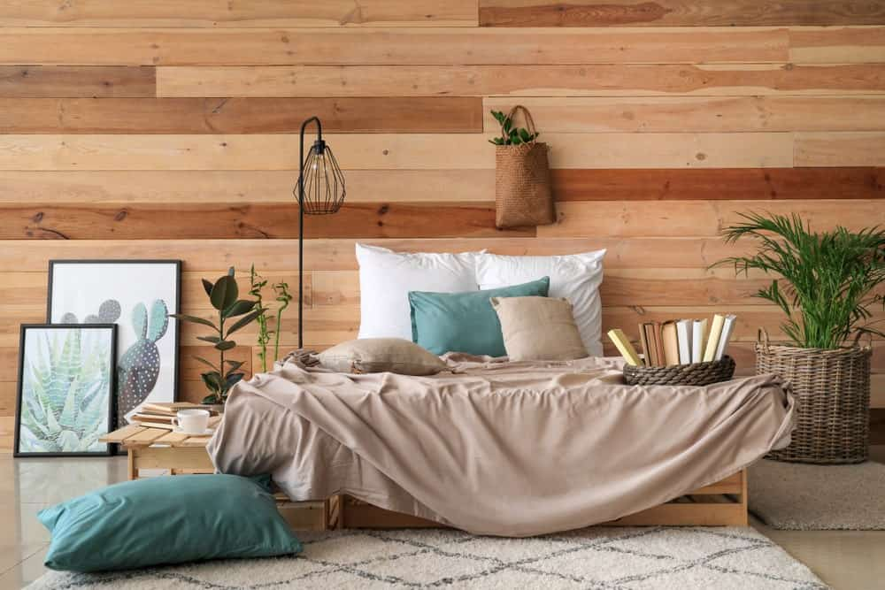 This master bedroom features succulent artworks and a cozy bed lighted by a black industrial floor lamp. It has a wood paneled wall and tiled flooring topped by taupe rugs.