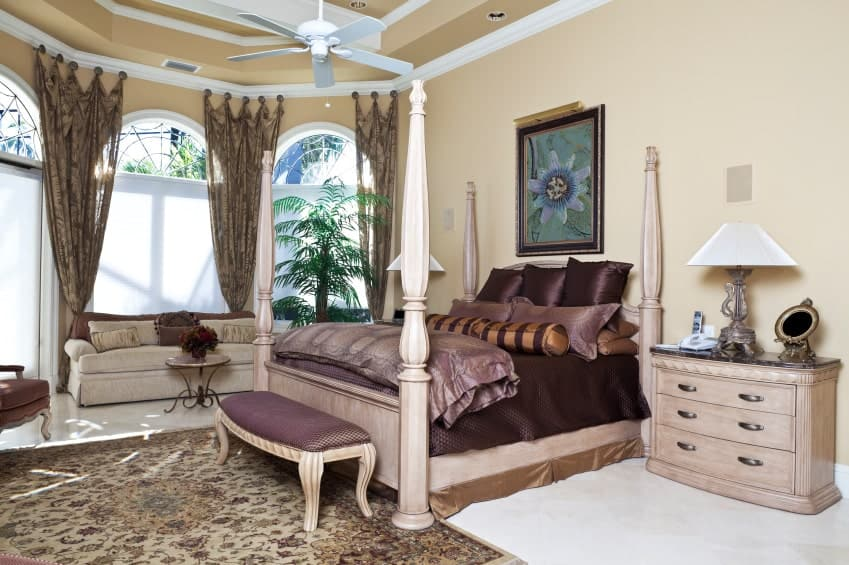 Elegant master bedroom showcases a wooden four poster bed and a beige skirted sofa by the arched windows dressed in tropical curtains. It includes floral wall art and a white fan that hung from the tray ceiling.