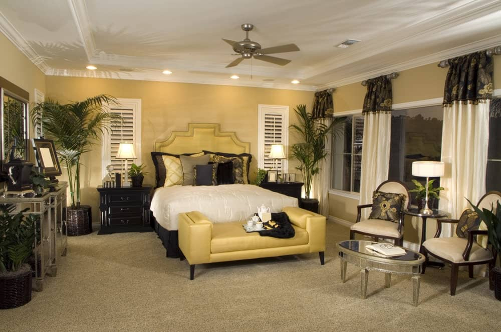 A yellow upholstered bench sits in front of the skirted bed in this master bedroom with a seating area showcasing cushioned chairs and an oval coffee table.