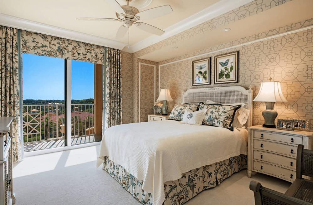 Classic master bedroom boasts lovely wall arts and a white wooden bed flanked by nightstands and table lamps. It has full height glazing covered in floral drapes and valance that match the bed skirt and pillows.