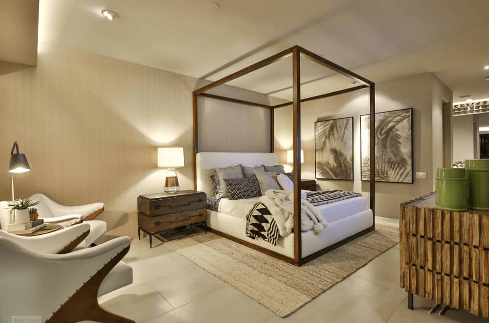 A wooden canopy bed sits on a jute rug in this master bedroom with stylish seats and rustic nightstands topped with glass table lamps.