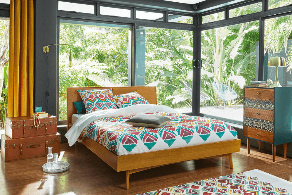 Tropical bedroom surrounded with panoramic windows that overlook the outdoor greenery. It has a gorgeous drawer chest and a wooden bed dressed in patterned bedding that complements the area rug.