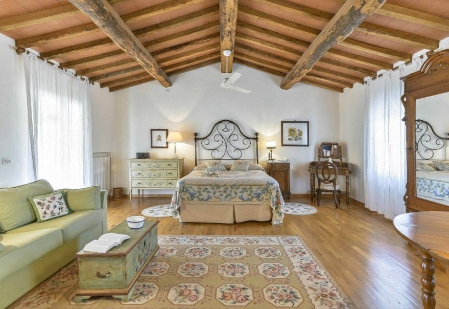 Spacious master bedroom featuring a wooden ceiling with exposed beams along with hardwood flooring. The room offers a classy bed along with an olive green couch on the side.