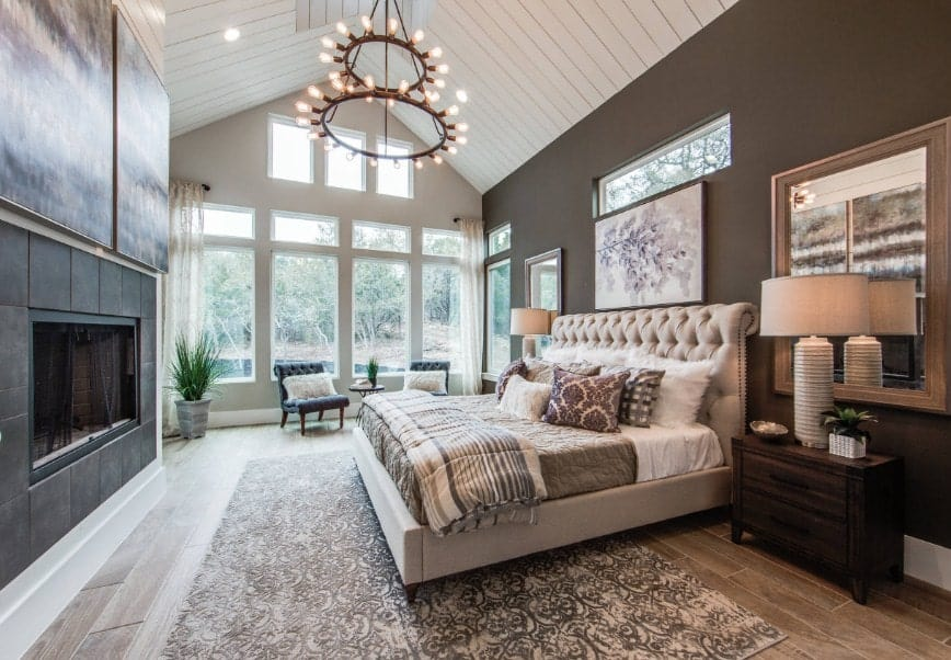 Large master bedroom featuring a tall ceiling and hardwood flooring. The room boasts a large luxurious bed along with a large fireplace.