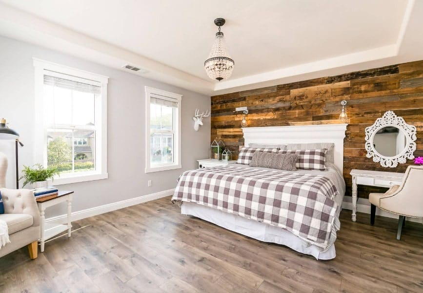 Large master bedroom with gray walls and a stylish rustic wall behind the bed. The room also features hardwood flooring and a tray ceiling.