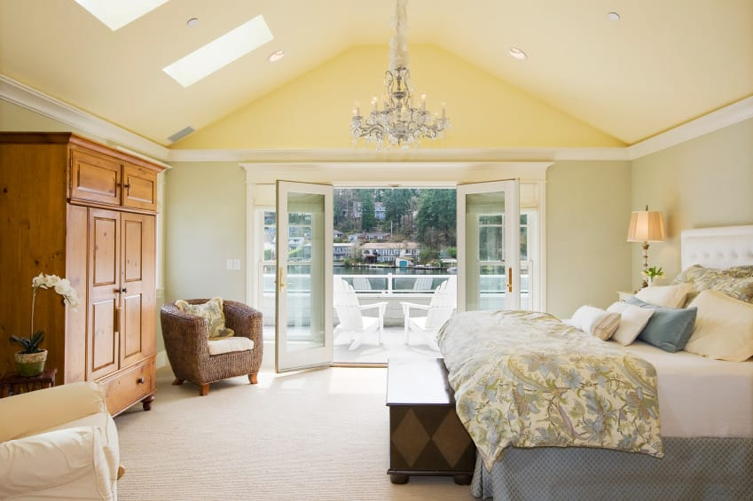 Spacious master bedroom featuring a vaulted ceiling with skylights and carpet flooring. The room has a large elegant bed lighted by table lamps and a gorgeous chandelier.
