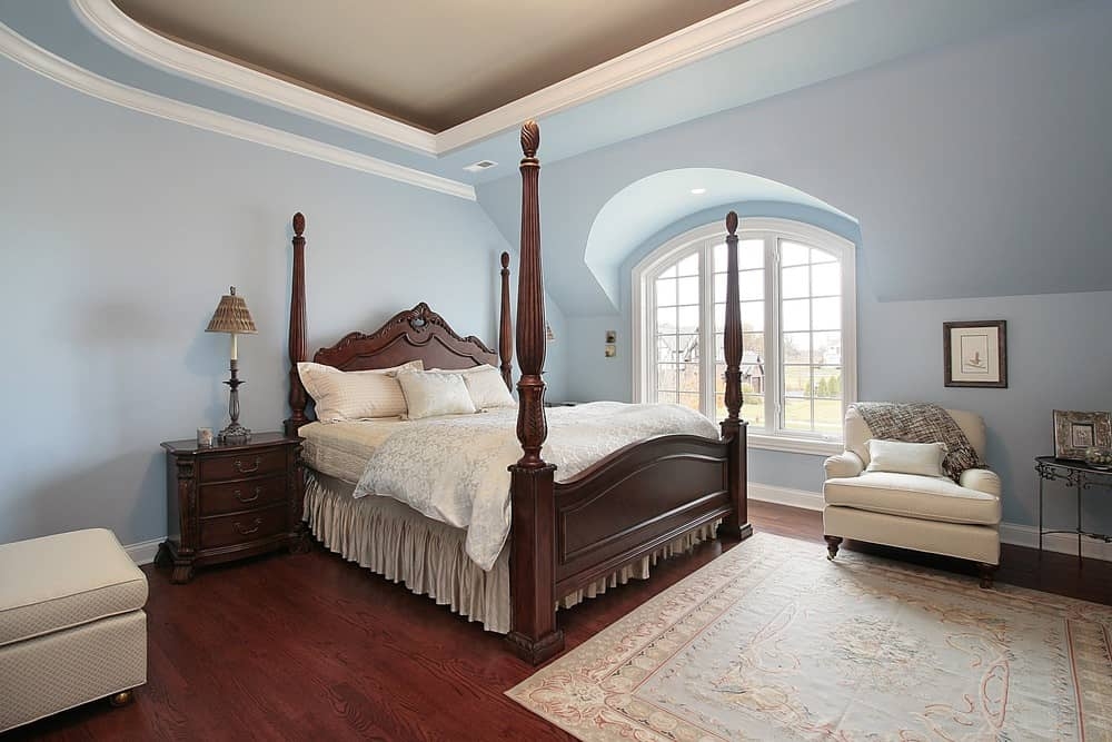 Large master bedroom with a classy tray ceiling along with hardwood flooring while sky blue walls surrounding the room. The bedroom has a large classy bed setup.