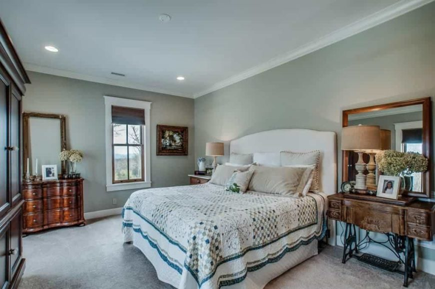 Master bedroom featuring carpet flooring and gray walls. It has a large comfortable bed lighted by two table lamps on both sides.