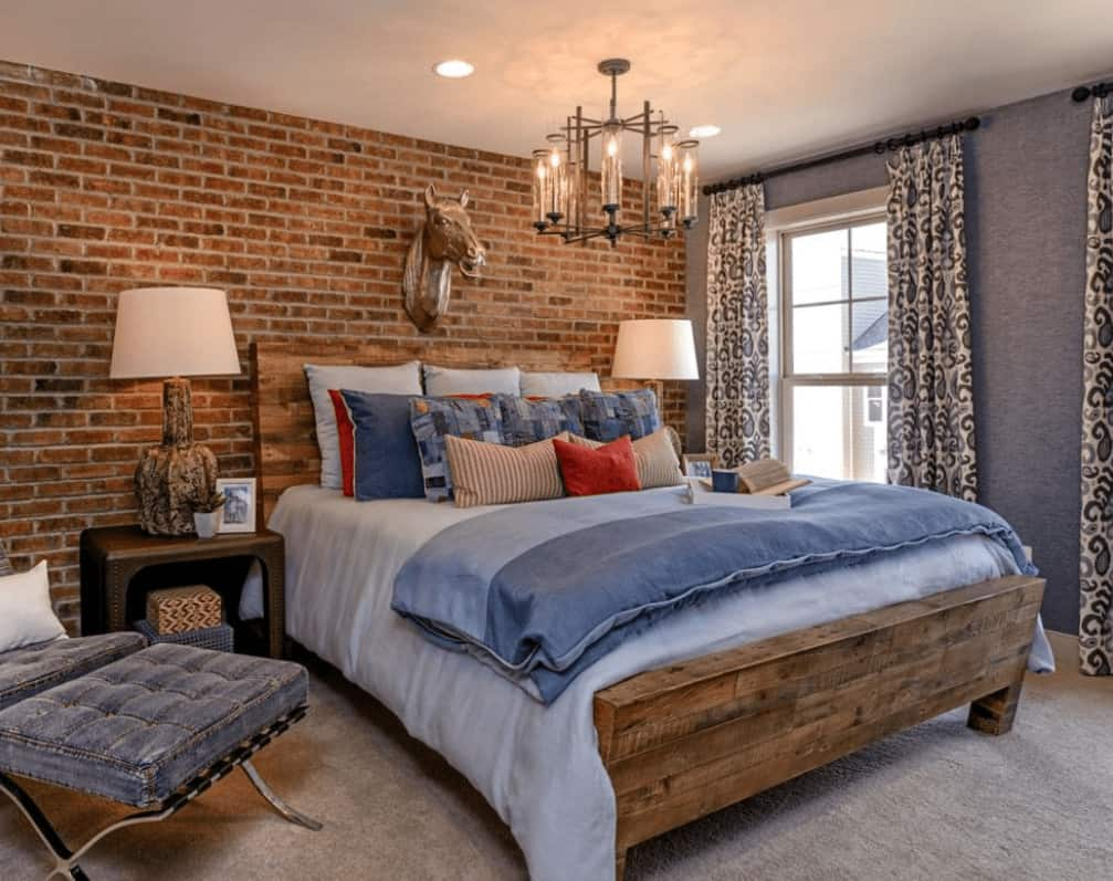 Stone brick accent wall adds texture in this primary bedroom featuring a tufted lounge chair and wooden bed illuminated by a glass chandelier.