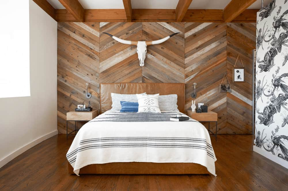 Southwestern bedroom boasts a brown leather bed in between metal nightstands along with a bull head decor mounted on the wood plank accent wall that's arranged in chevron pattern.
