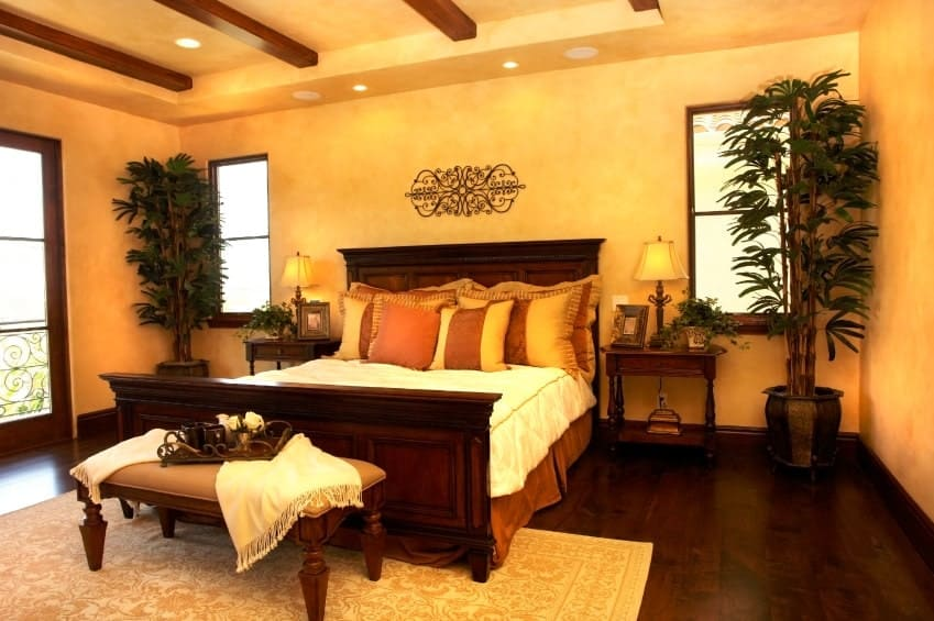Tall potted plants create a tropical feel in this southwestern bedroom with a wooden bed and beige cushioned chair that sits on a classic area rug over dark hardwood flooring.