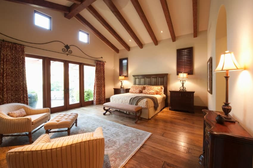 Southwestern bedroom with wide plank flooring and cathedral ceiling lined with wood beams. It includes a wooden bed and striped armchairs paired with a matching tufted ottoman.