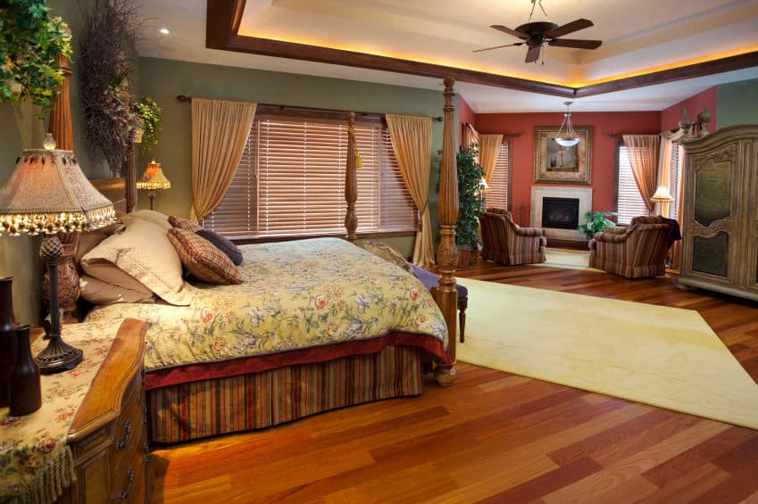 This primary bedroom features a four poster bed and a seating area by the fireplace illuminated by a dome pendant light. It has a tray ceiling and rich hardwood flooring topped by a beige area rug.