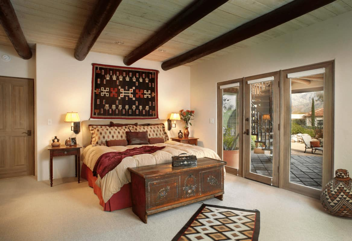Southwestern bedroom showcases wood beam ceiling and carpet flooring topped by a patterned runner. It has a black tapestry and red skirted bed with a rustic console table on its end.